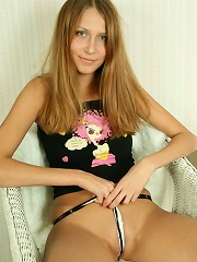 Cute teen takes off her clothes and spreads her long legs